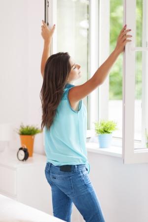Jonge vrouw het openen raam in de woonkamer Stockfoto