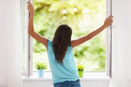 ventana abierta: Mujer joven respirar aire fresco durante el verano