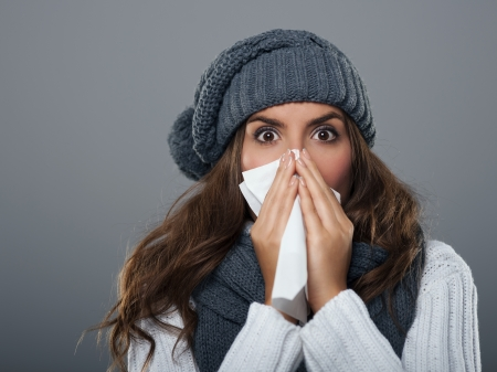 cold remedy: Young woman wearing warm hat sneezing
