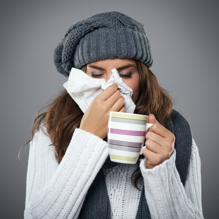 Young woman having flu and blowing her nose at handkerchief photo