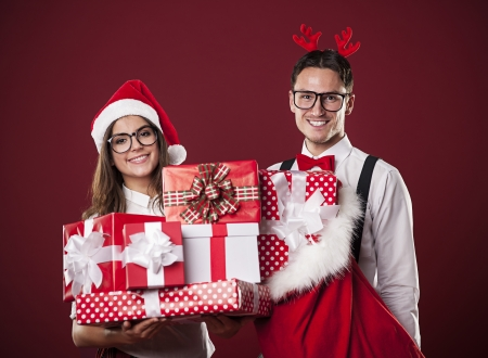 Portrait of smiling couple with stack of christmas presents  photo