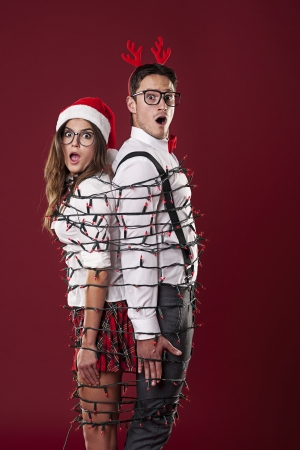 Funny nerd couple are tangling  in christmas lights