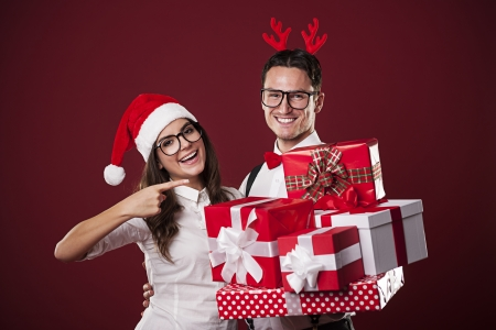 Smiling nerd couple showing christmas gift  photo