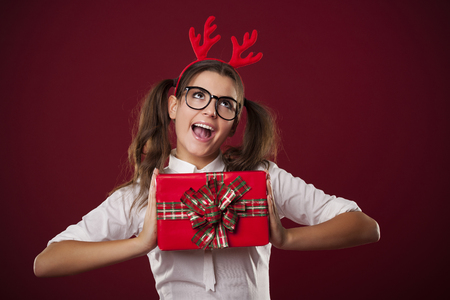 Nerdy woman holding red christmas present   photo