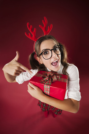 Shocked nerdy woman pointing at christmas gift  photo