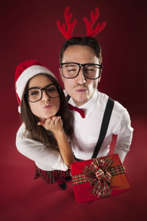 Nerd couple blowing kisses in christmas time  photo