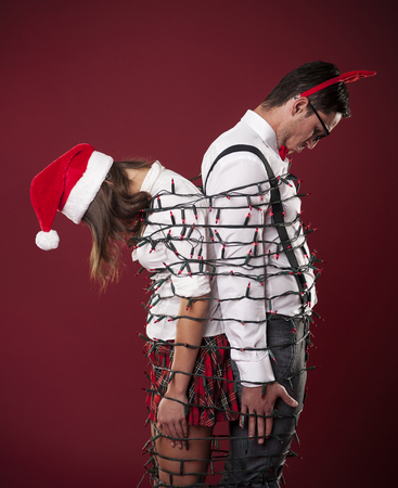 tangling: Loser nerd couple are tangling in christmas lights  Stock Photo