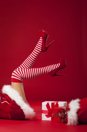Mrs santa claus legs in striped stockings with christmas gifts  photo