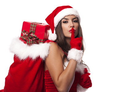 Sexy santa claus woman with christmas sack saying shh photo