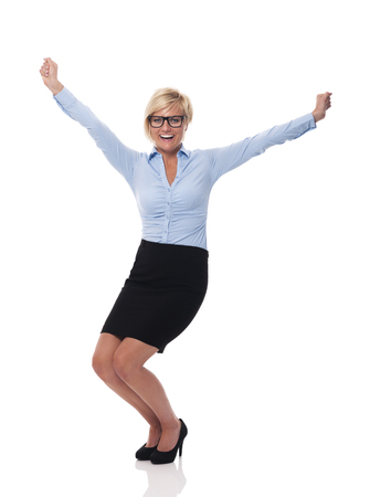 Excited young businesswoman with hands raised  photo