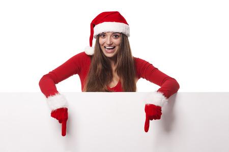wearing santa hat: Excited woman wearing santa hat showing on blank billboard