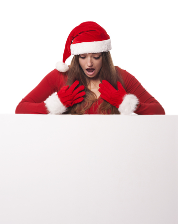 Shocked santa woman looking down on whiteboard   photo