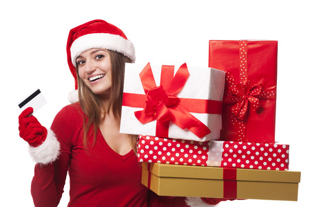 Woman wearing santa hat holding christmas gifts and credit card photo
