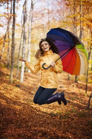 Young woman jumping during the rainy day at autumn   photo