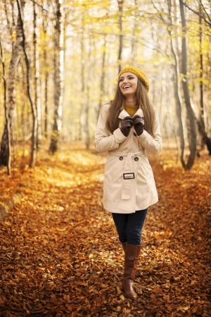 Smiling woman walking in park at autumn season