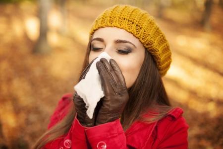 Vrouw niezen in de zakdoek bij de herfst Stockfoto