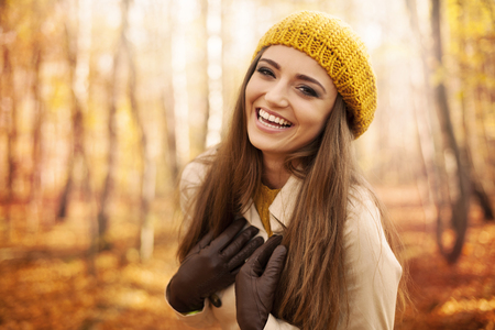 open trench: Young woman wearing autumn clothes laughing in park  Stock Photo