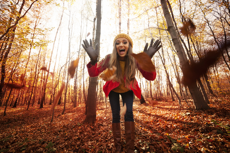Young woman have fun with autumn leaves photo