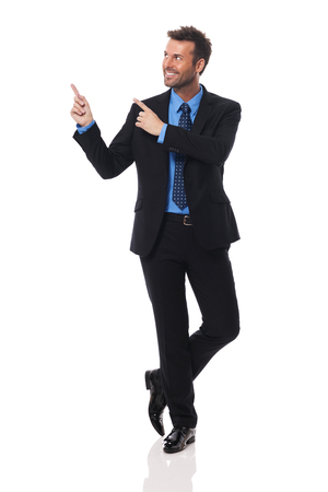 Handsome and smiling businessman pointing at copy space    Stock Photo