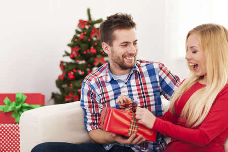 Happy couple have fun during the opening christmas present photo
