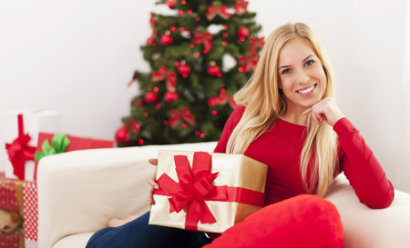 Beautiful blonde woman sitting in living room during the christmas time photo