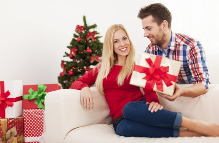 Handsome man surprising his girlfriend with christmas present  photo