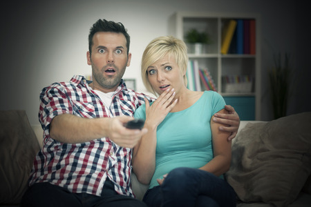 scared woman: Scared couple watching horror film