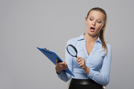 Shocked woman looking at office documents with magnifier photo