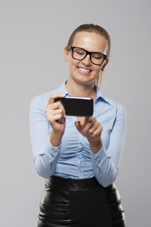 Happy young business woman text messaging on smart phone photo