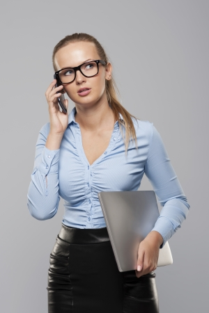Busy businesswoman with modern electronic equipment photo