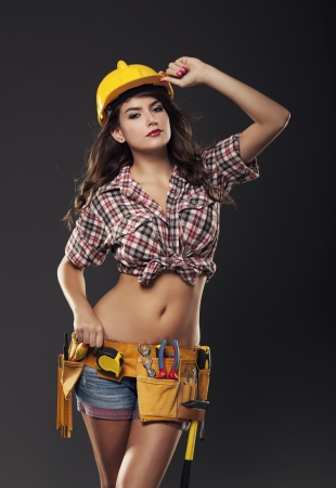 Passionate female construction worker wearing yellow hardhat photo