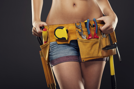 Close up of  female construction worker with tool belt photo