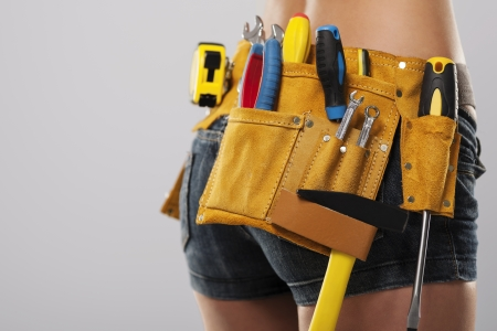 Close up of female construction worker with tool belt Imagens