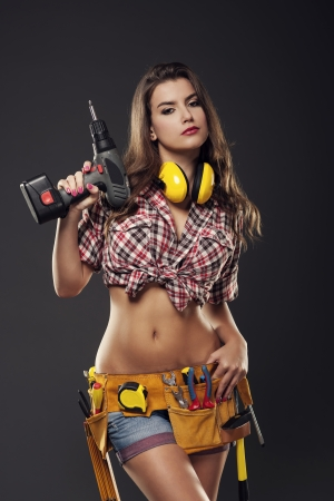 Passionate female construction worker is ready for drilling  photo