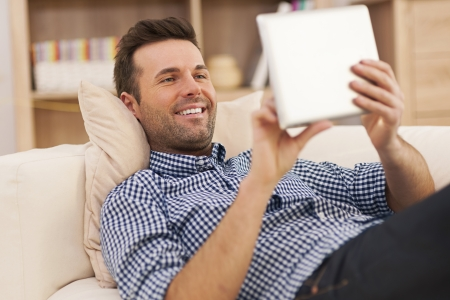 man lying down: Happy man relaxing on sofa with digital tablet