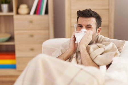 cold room: Man blowing his nose while lying sick in bed Stock Photo