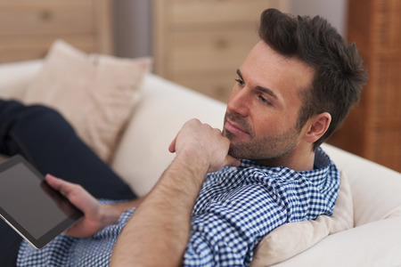 Handsome and pensive man with digital tablet Stock Photo - 24831174