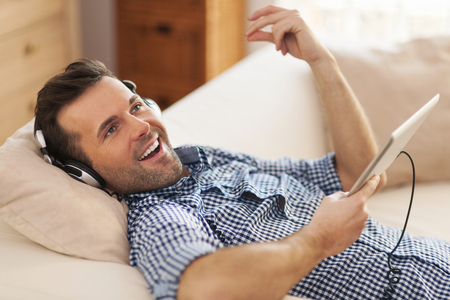 Happy man listening music and lying down on sofa   photo