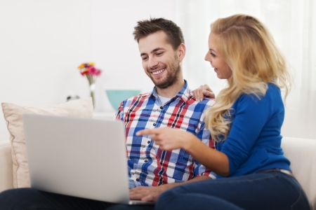 Happy couple using computer at home Stock Photo - 24831576