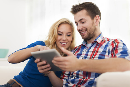Smiling couple using digital tablet at home Stock Photo - 24831581
