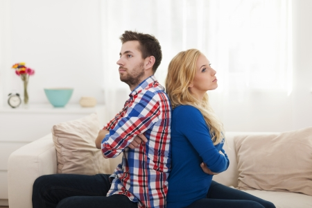 relationship problems: Angry young couple sitting back to back at home  Stock Photo