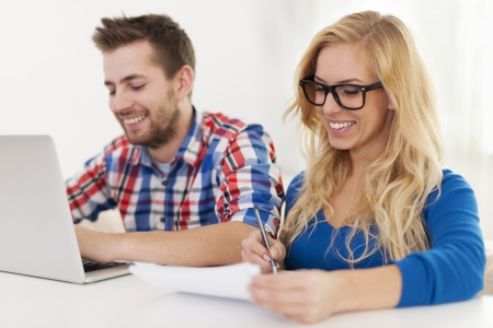 Smiling couple paying bills at home photo