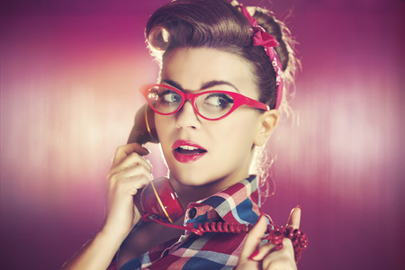 Beauty young pin-up woman with retro telephone photo