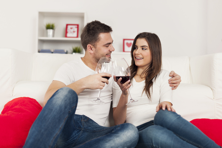 Happy couple spending romantic time with red wine at home  photo