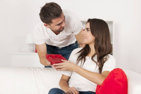 Affectionate man giving his girlfriend small red gift Stock Photo - 24908099