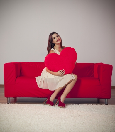 Beautiful young woman with big heart pillow photo