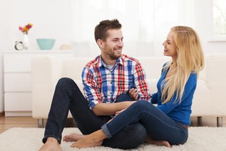 barefoot man: Loving couple sitting on floor in living room