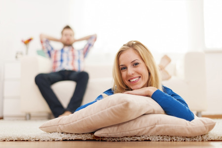 Happy young woman lying down on carpet at home   Stock Photo - 24962928