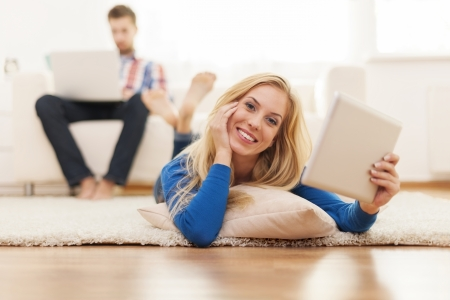 Smiling woman lying on carpet and using digital tablet   photo