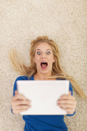 femme bouche ouverte: Surprise jeune femme couchée sur le tapis et en utilisant tablette numérique